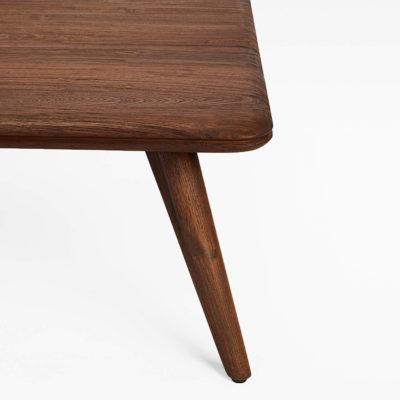 Close up of the Beluga coffee table showing the top corner, exposed teak grain detail, grooved egde & retro legs