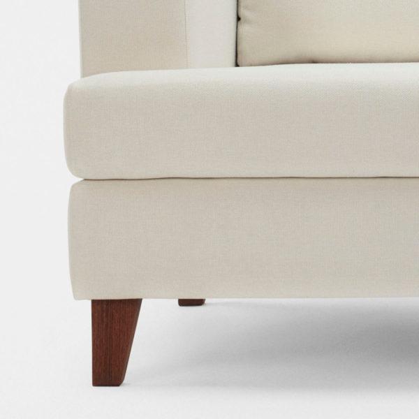 Close up of the Plush Comfort sofa showing the teakwood leg detail